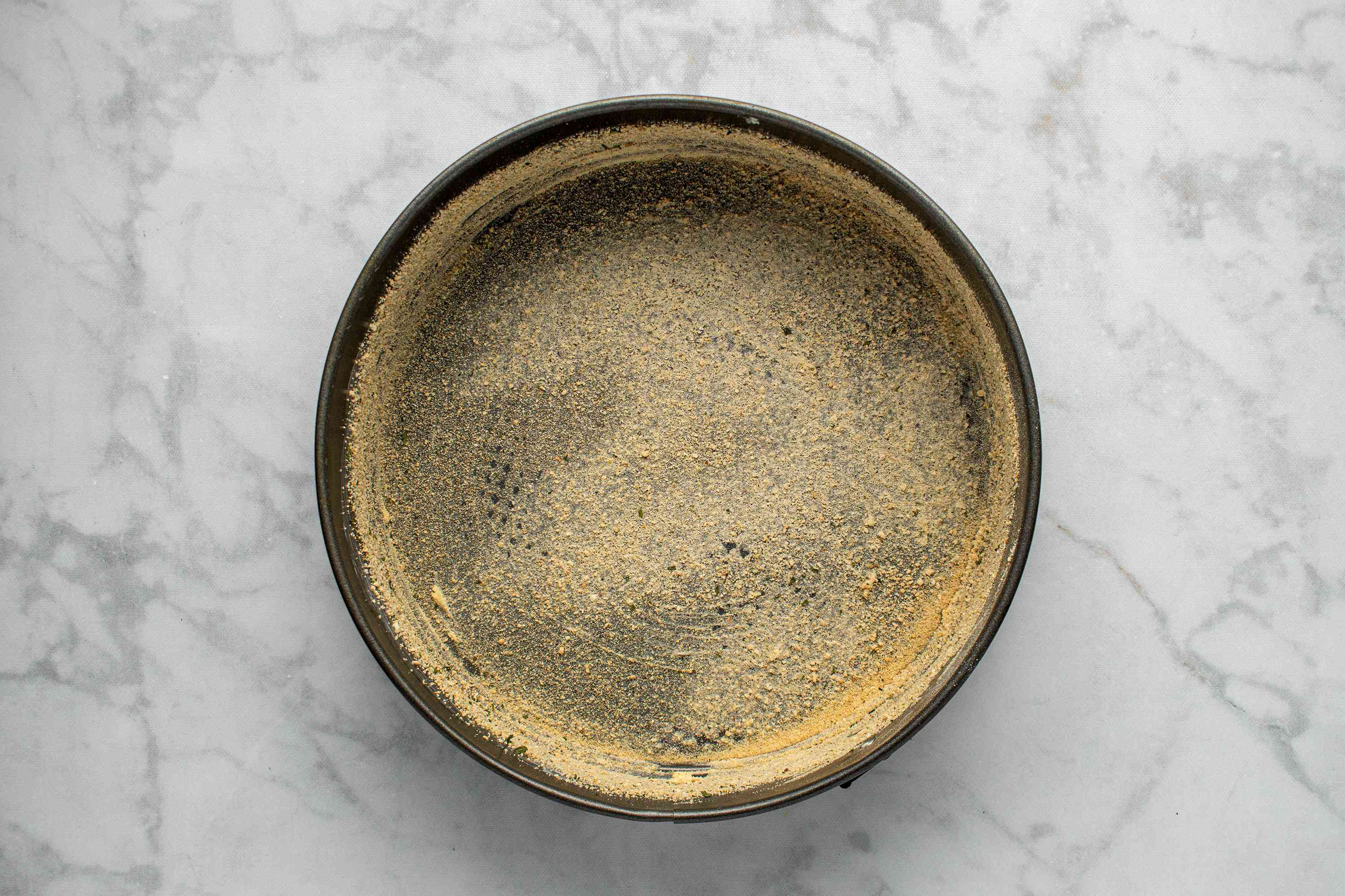 buttered springform pan with breadcrumbs