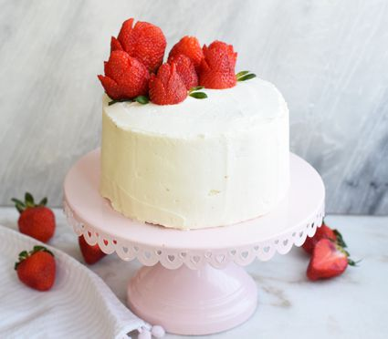 vanilla and strawberry cake on a cake platter with strawberry roses