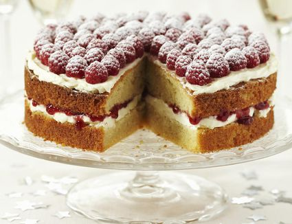 White cake with raspberries on cake stand