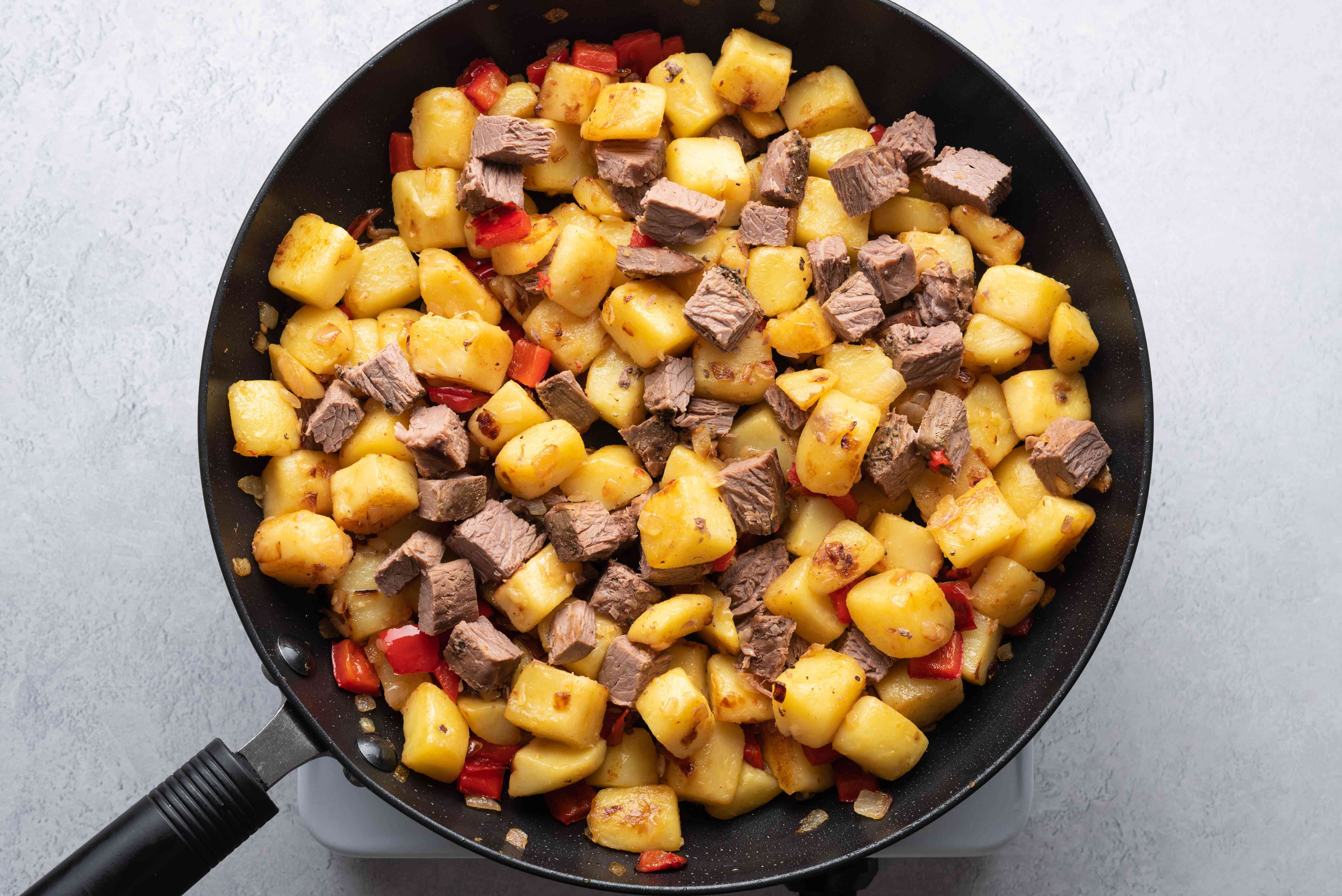 brisket added to the potato mixture in the pan