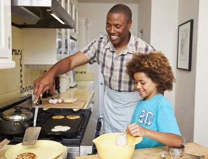 dad cooking pancakes with daughter