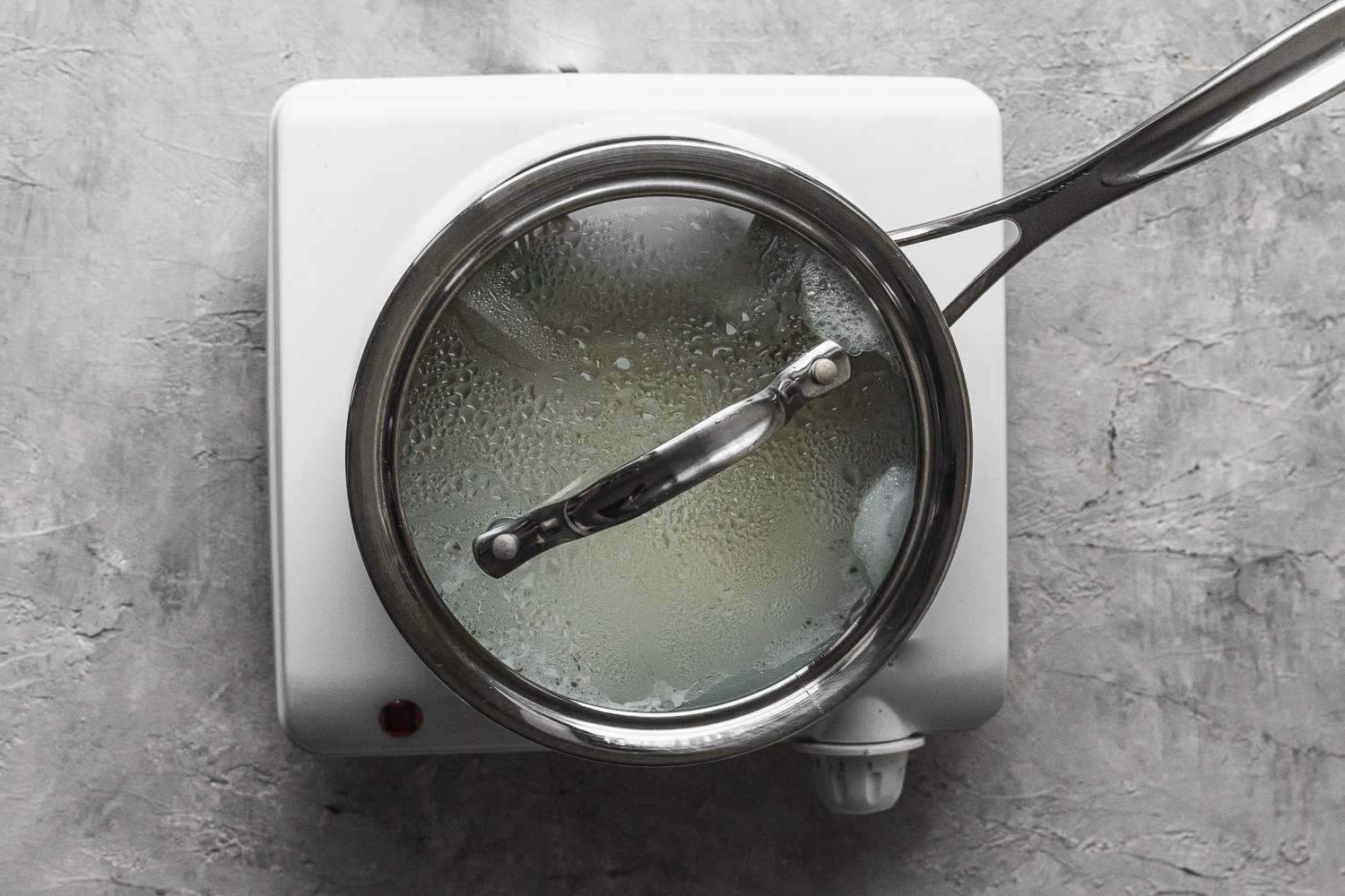 rice cooking in a covered saucepan