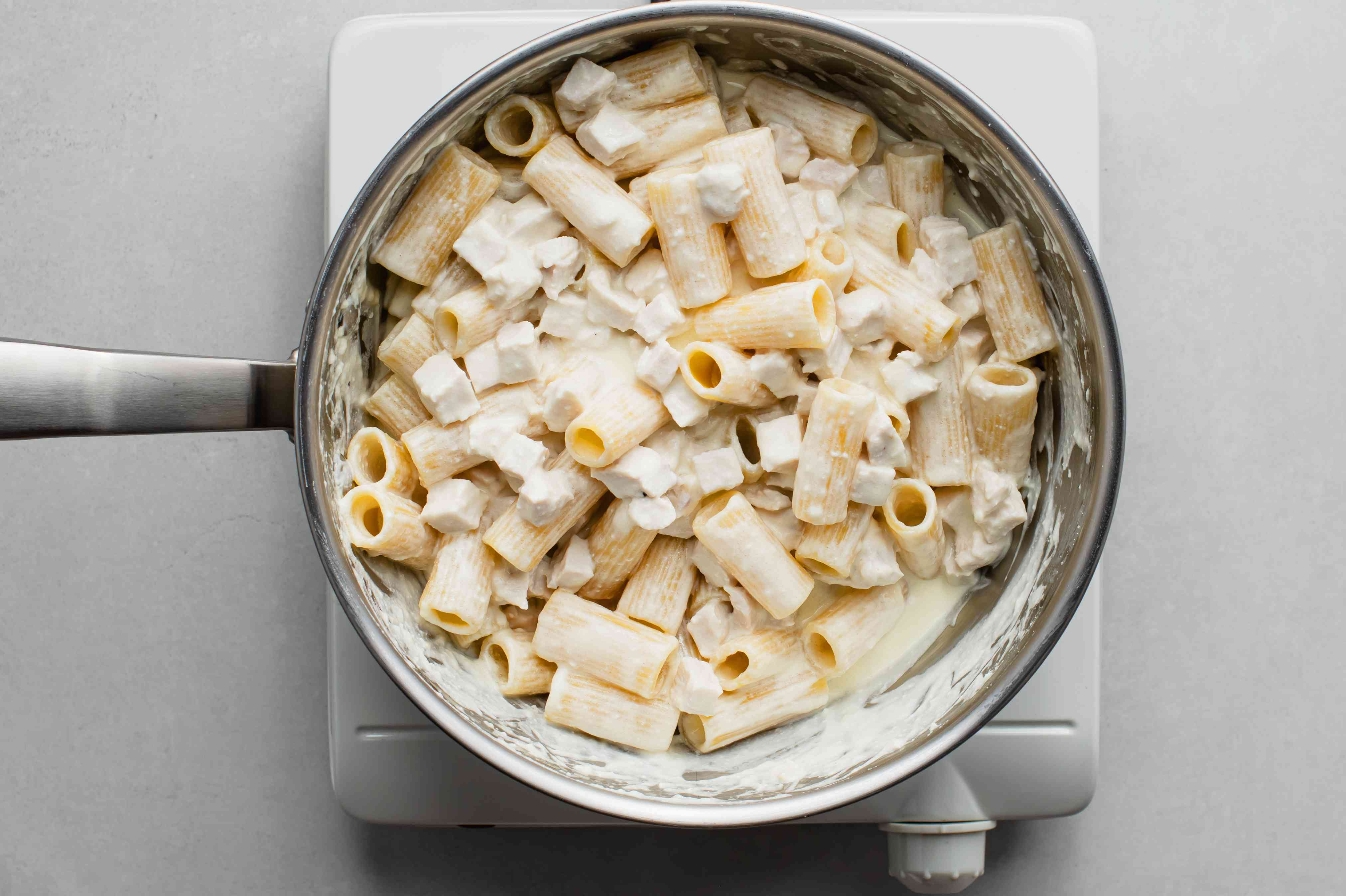 pasta mixed with Alfredo sauce in a pot