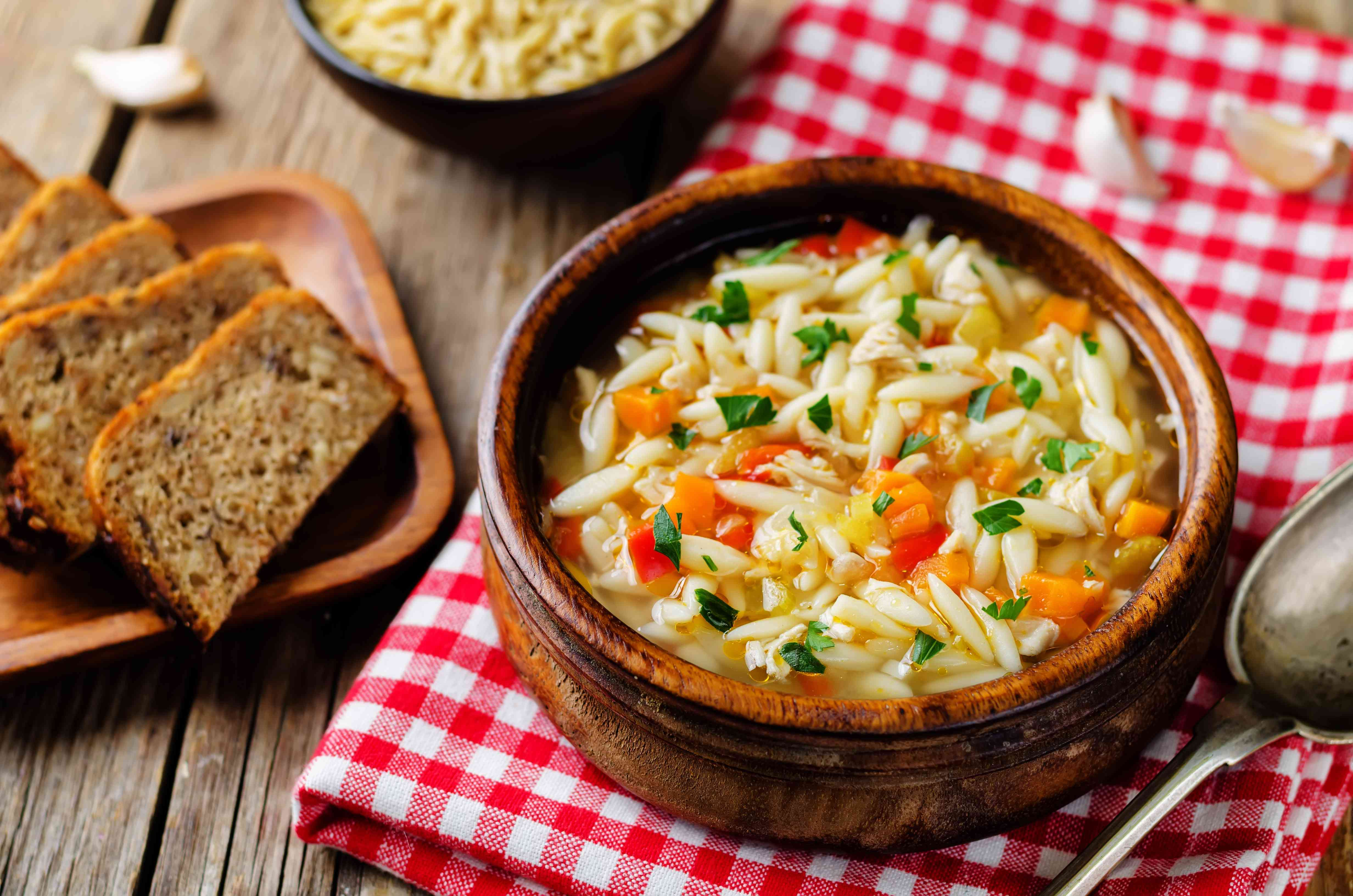 Turkey orzo vegetables soup with fresh rye bread slices