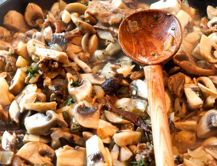 Sauteeing mushrooms in a pan on a gas stove with a wooden spoon