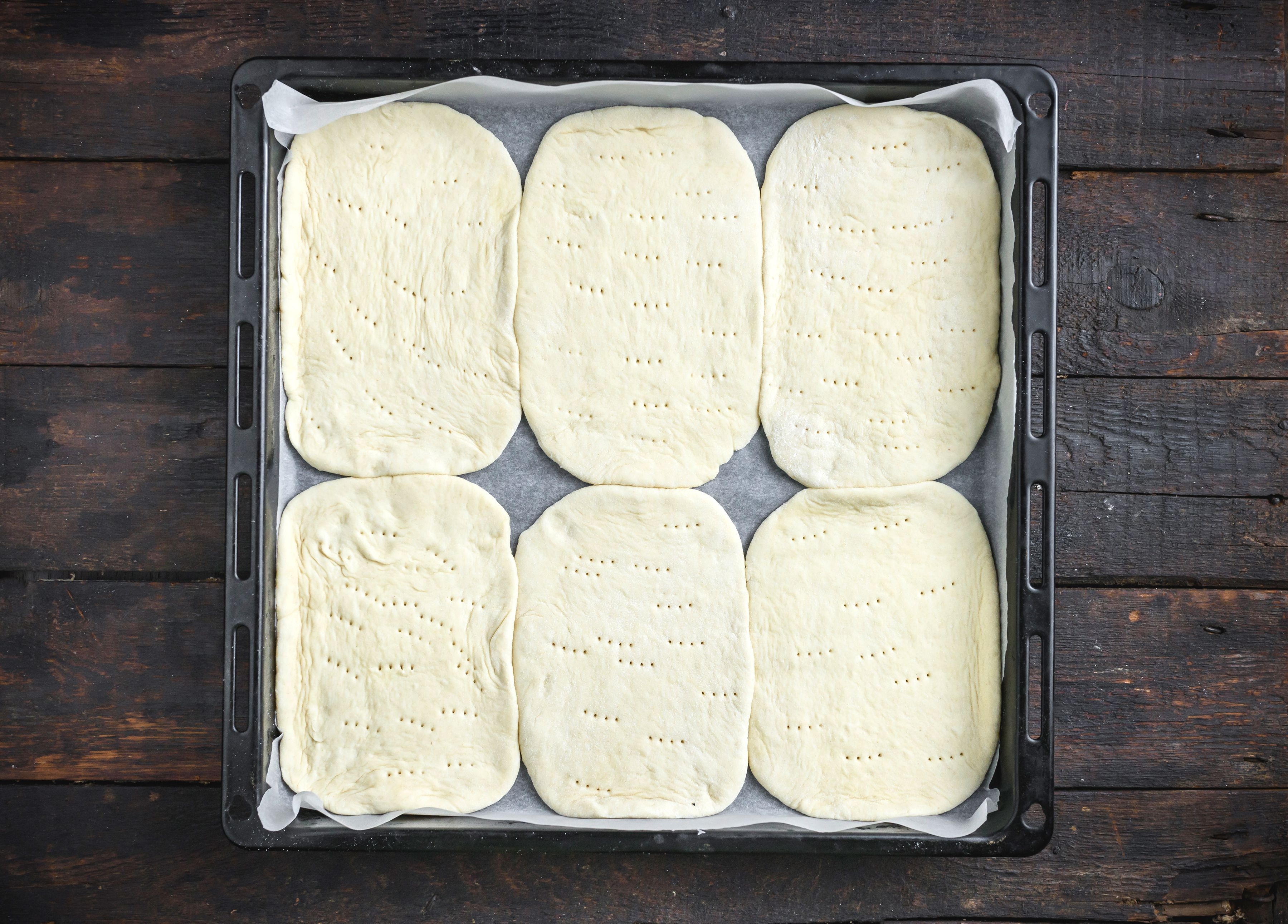 Transfer dough, pricked with fork tines, to baking sheets