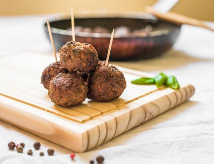 Meatballs on a wooden board with toothpicks against white background