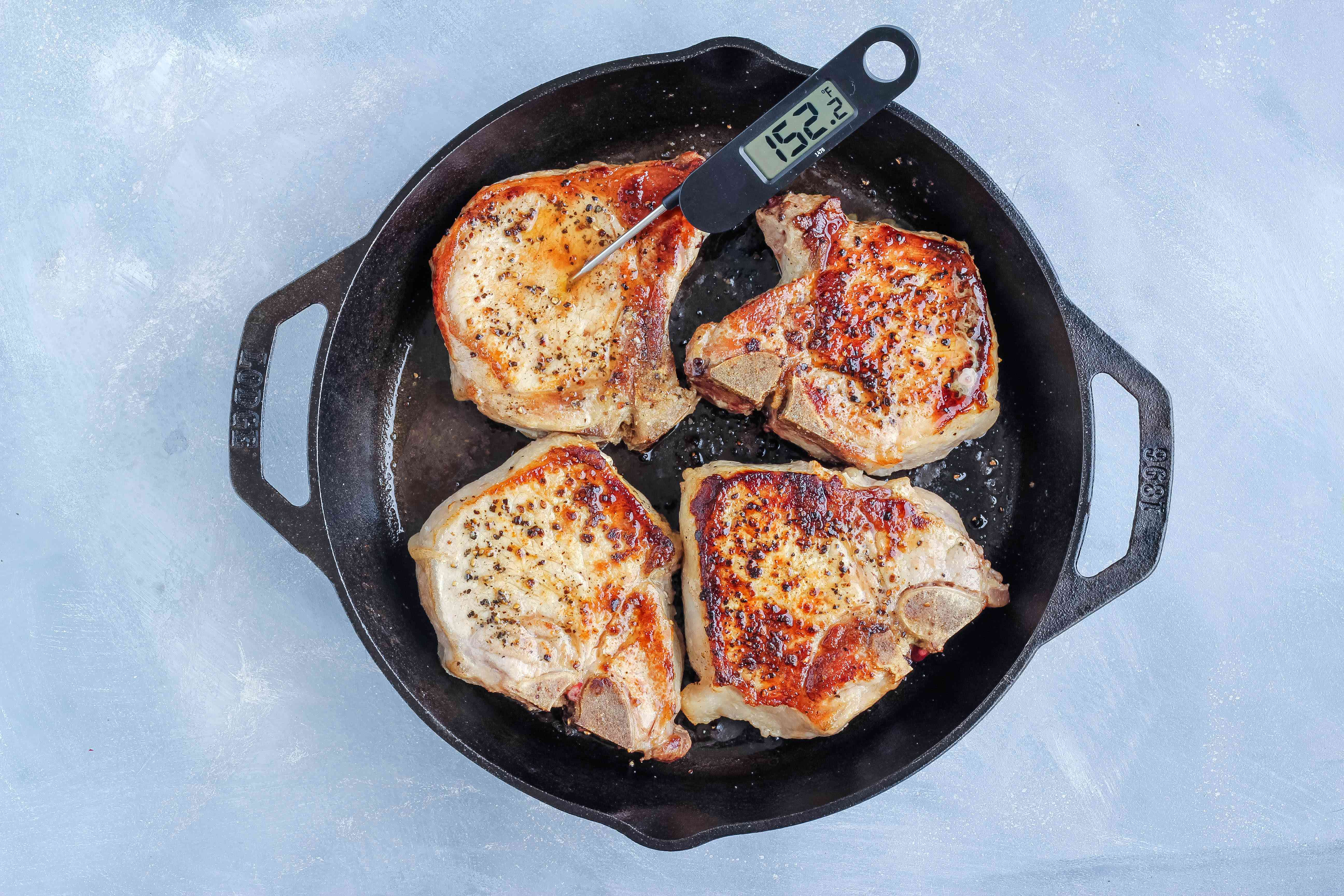 Testing pork chops with an instant-read thermometer