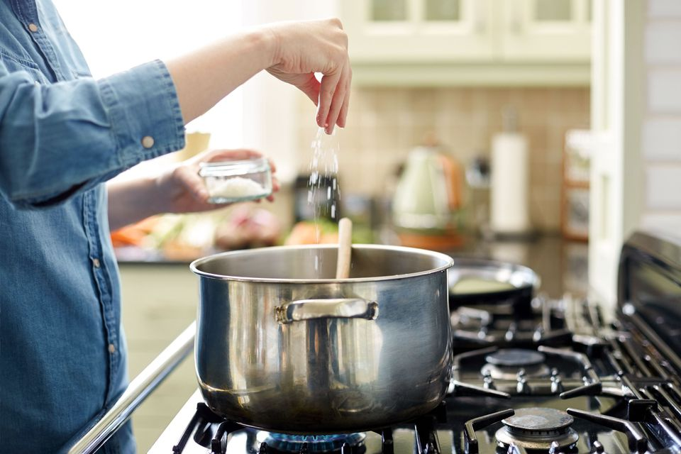 A woman adding salt to a simmering pot