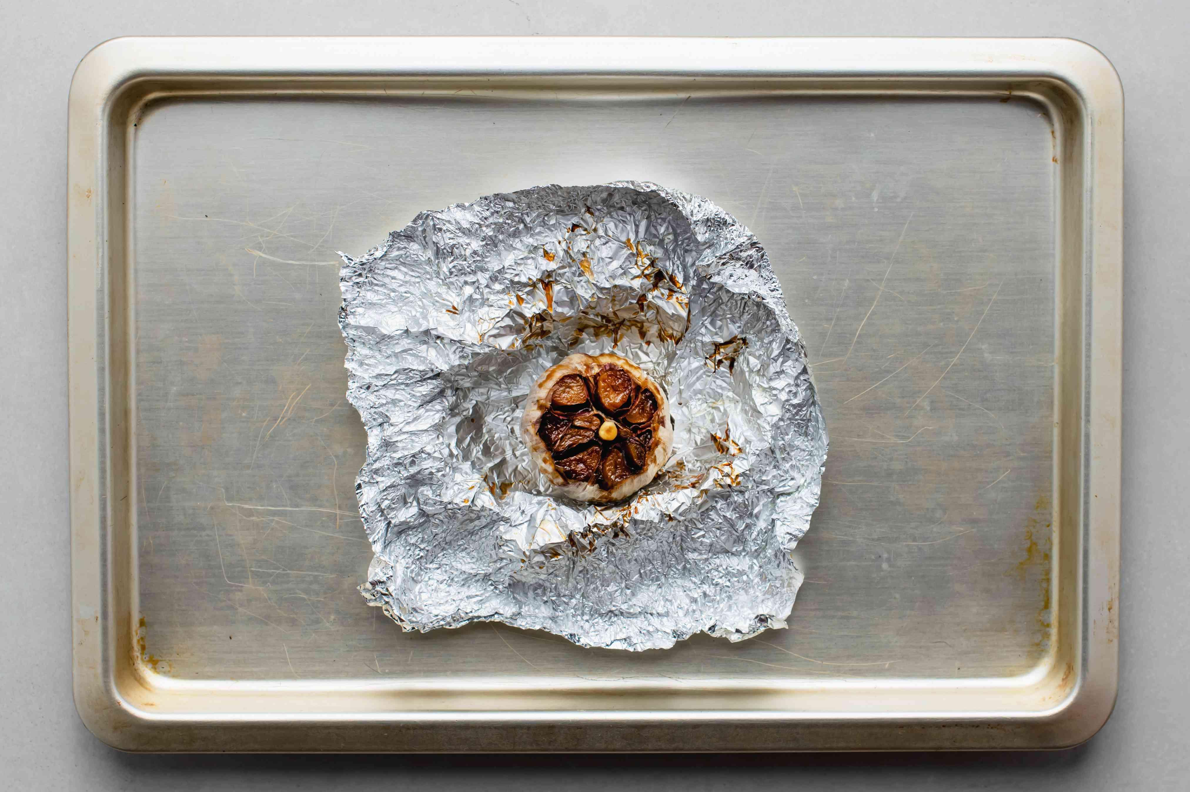 Roasted garlic cooling on a baking sheet