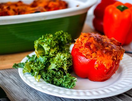 Stuffed peppers on a plate with kale