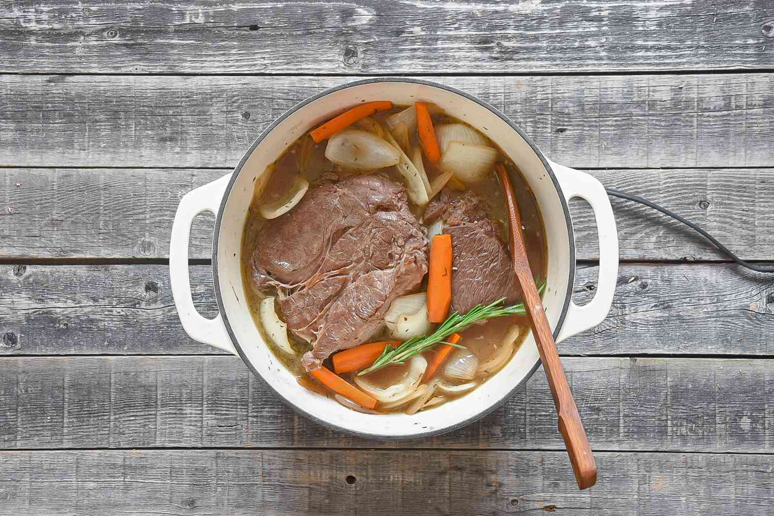 Pot roast cooking in the beef broth and wine, with carrots and onions, in a large white pot