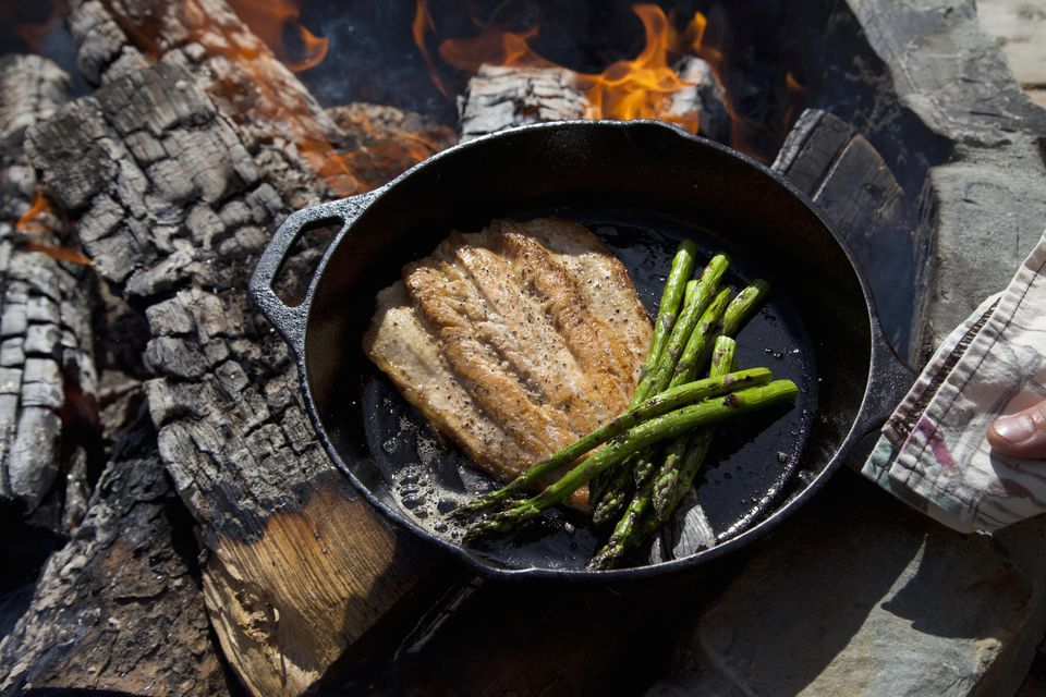 Trout filet and asparagus in cast iron fry pan.