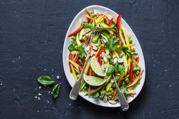 Raw vegetables Pad Thai salad on dark background, top view. Vegetarian healthy food. Copy space