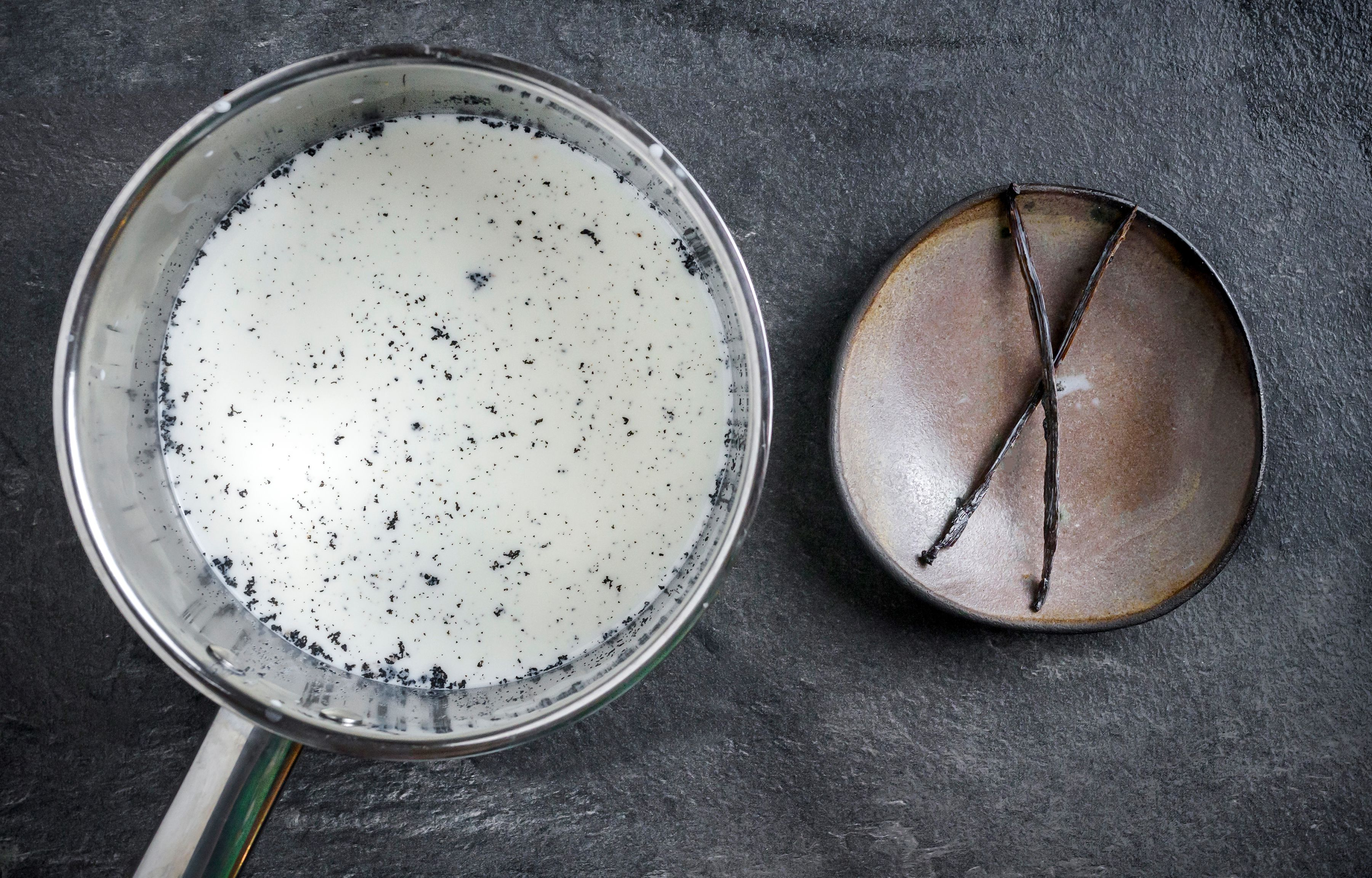 Vanilla bean and milk in saucepan