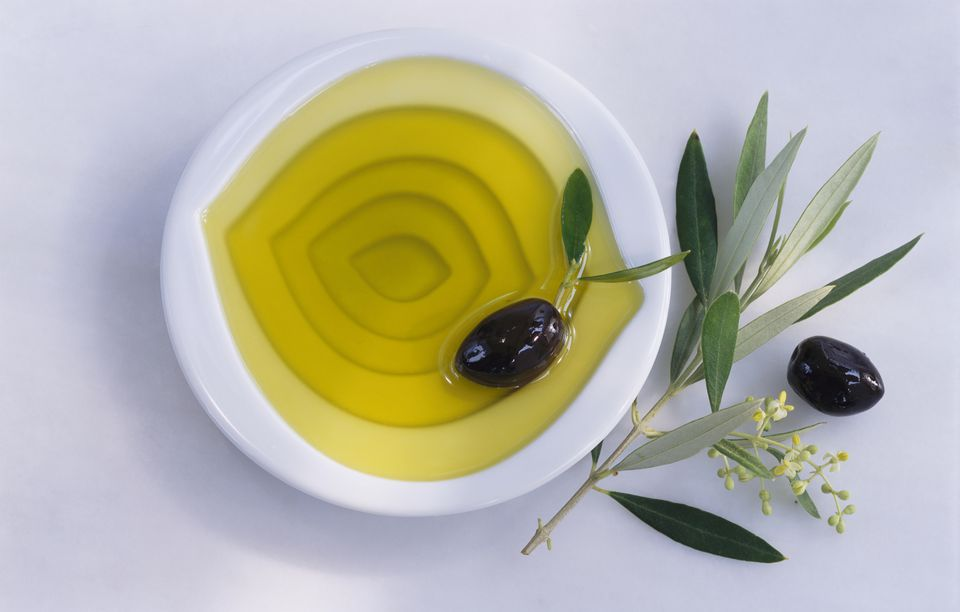 Olive oil in white bowl with black olives