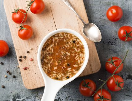 Bowl of tomato soup and rice on chopping board