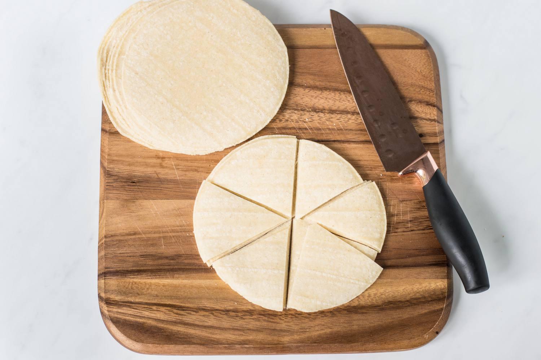 Corn tortillas cut into wedges on cutting board