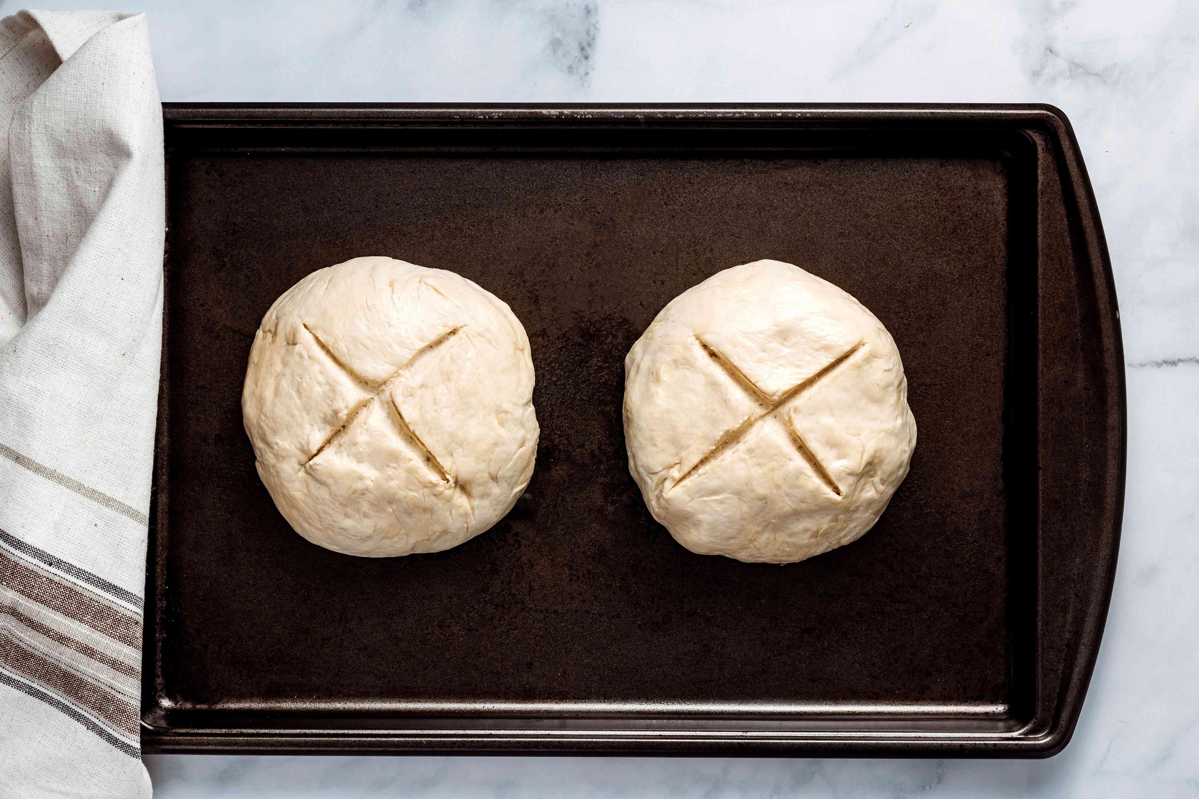 dough on a baking sheet, an X sliced into the dough