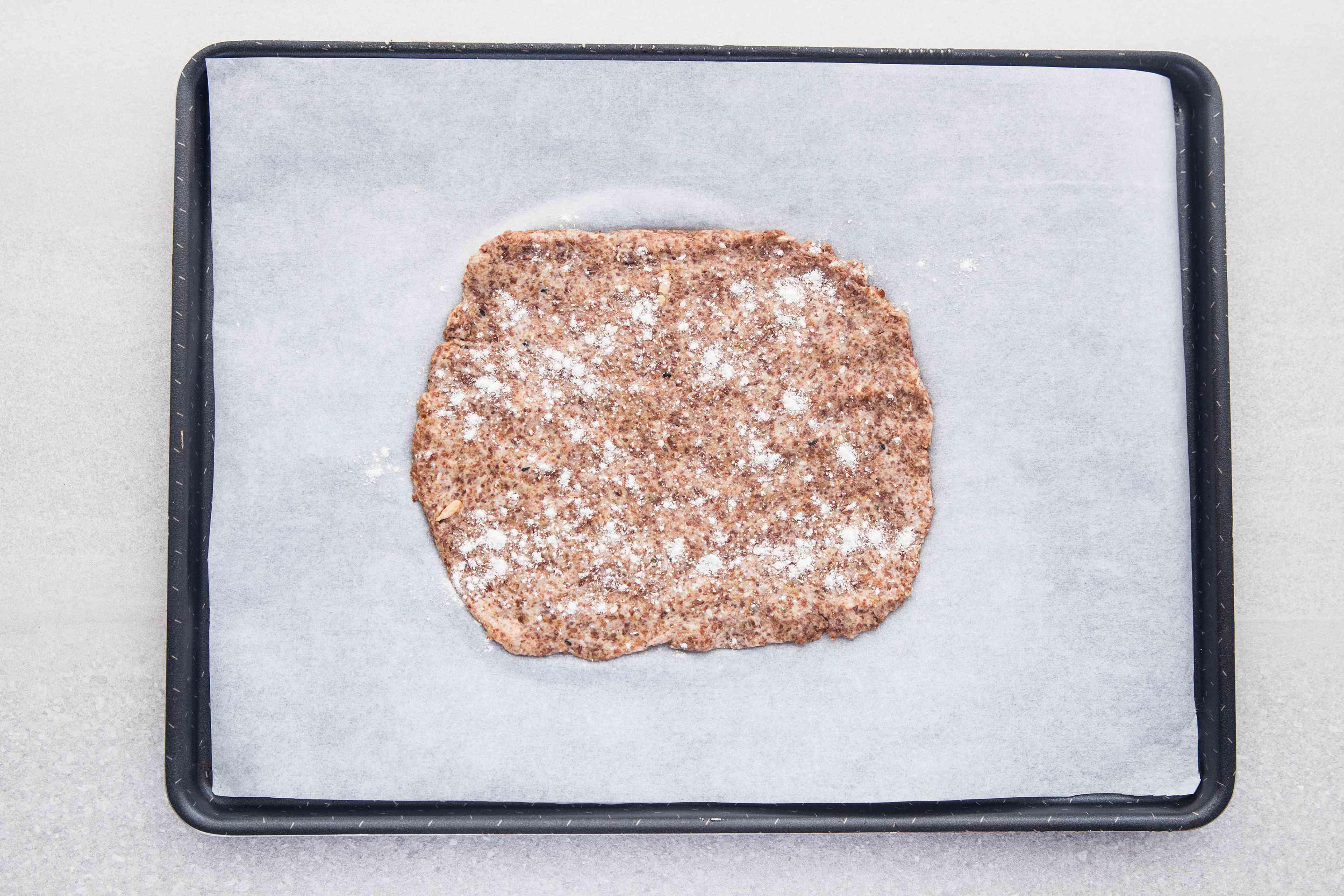 Cracker dough with flour on top on a baking sheet
