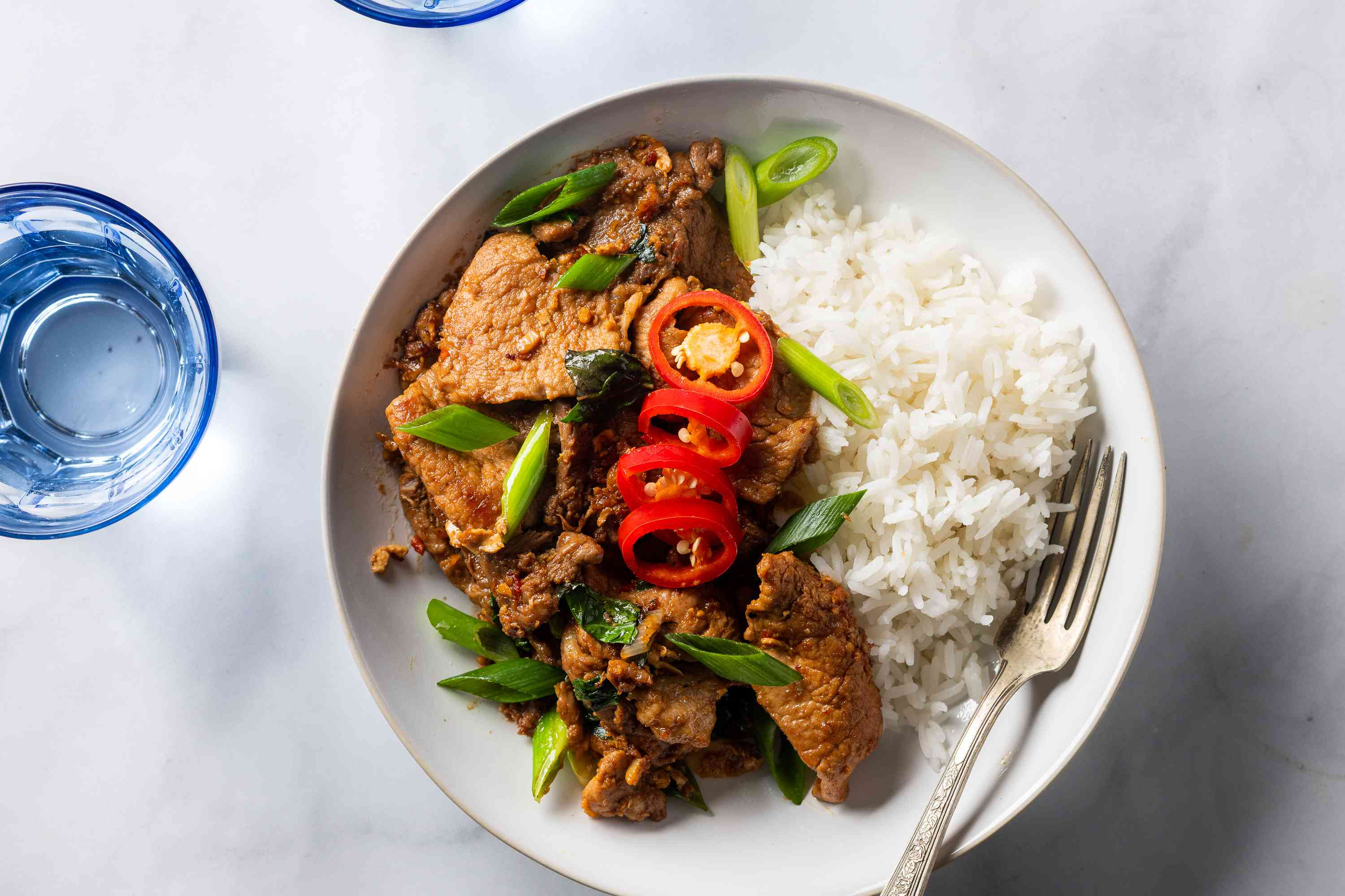 Thai basil pork with rice on the side on a plate with a fork