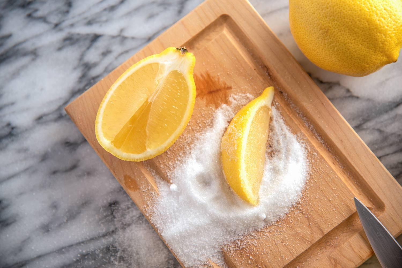 Lemon wedge coated in sugar on a cutting board