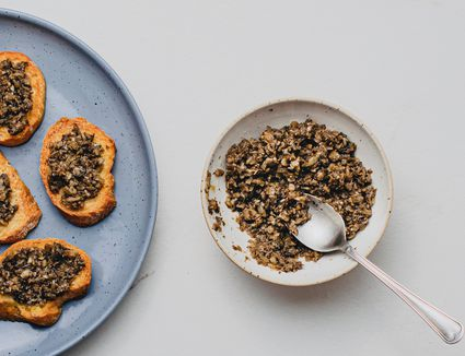 Mushroom Duxelles Recipe, mushroom mixture in a white bowl, mushroom duxelles on top of toasted bread on a blue plate