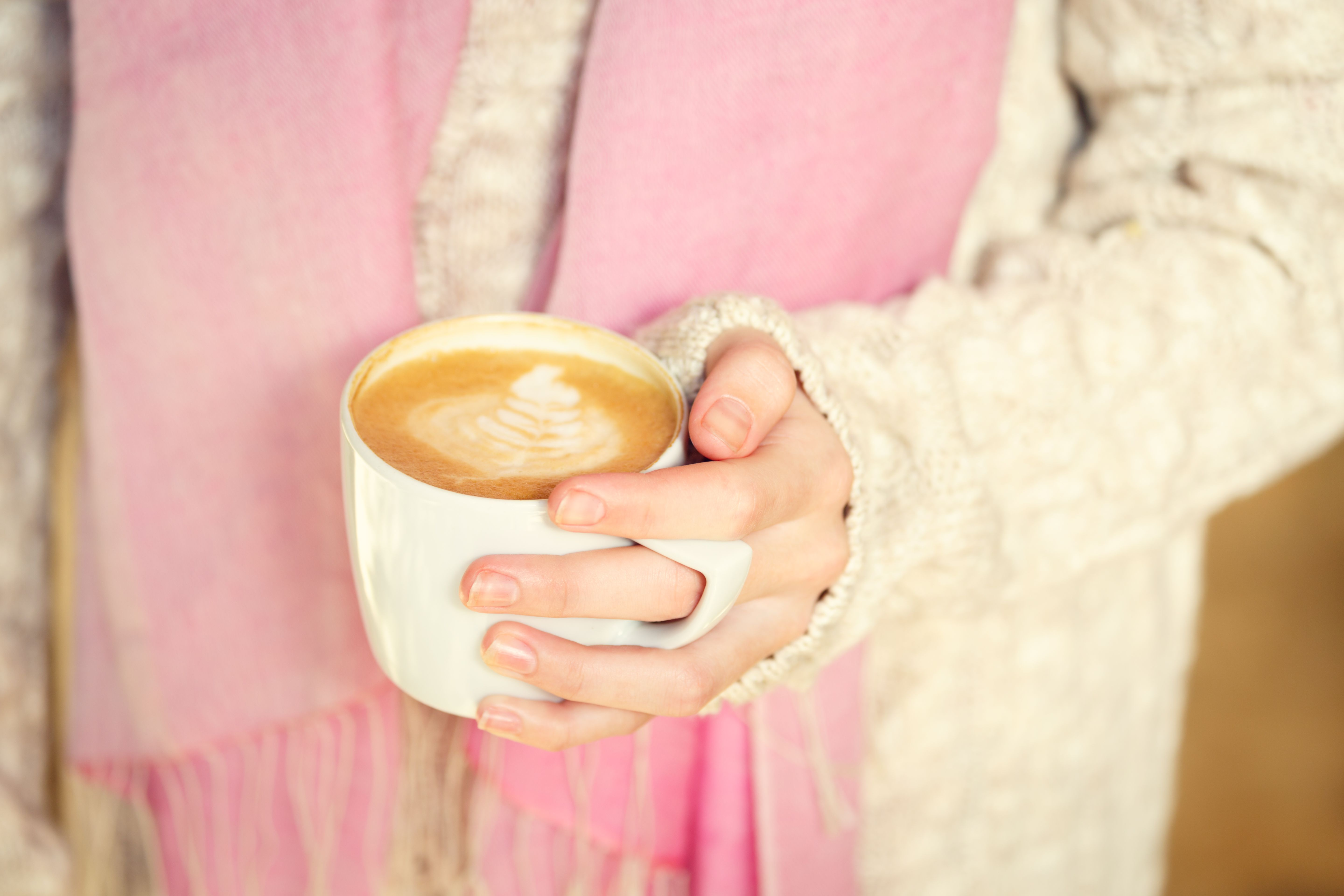 Girl holding a cup of coffee or hot chocolate or chai tea latte. Quiet hygge time concept