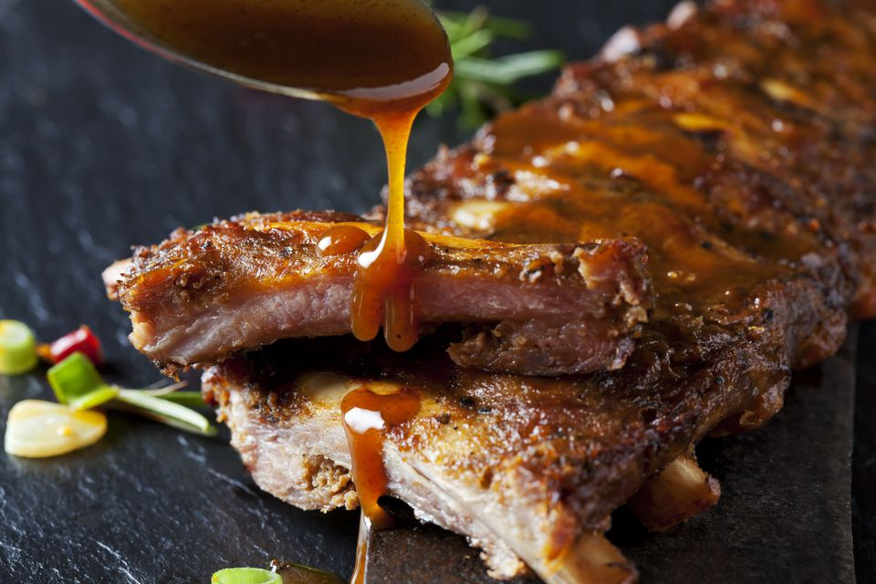 Barbecue sauce dripping on marinated and grilled ribs