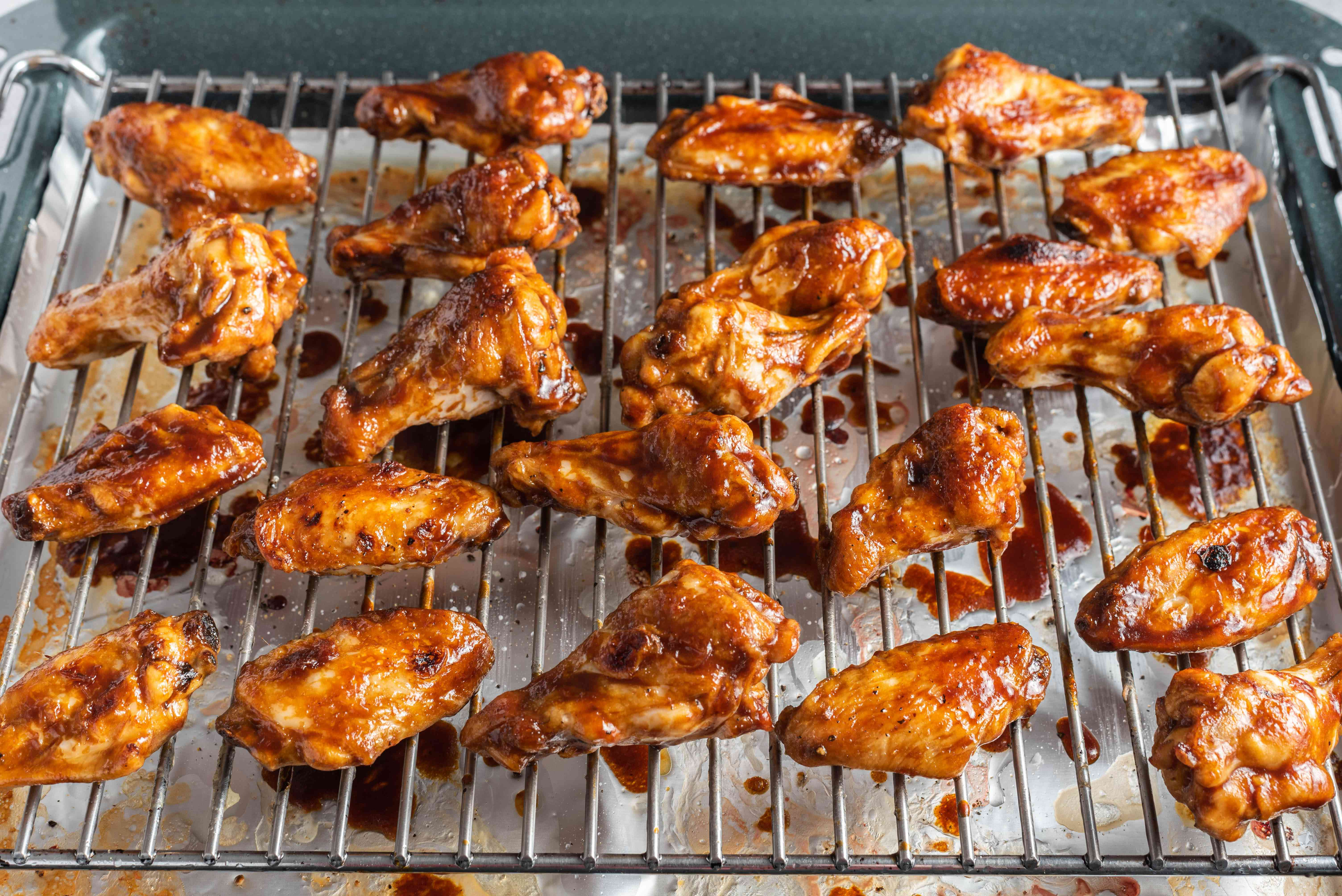 Chicken wings coated in barbecue sauce on a broiling rack