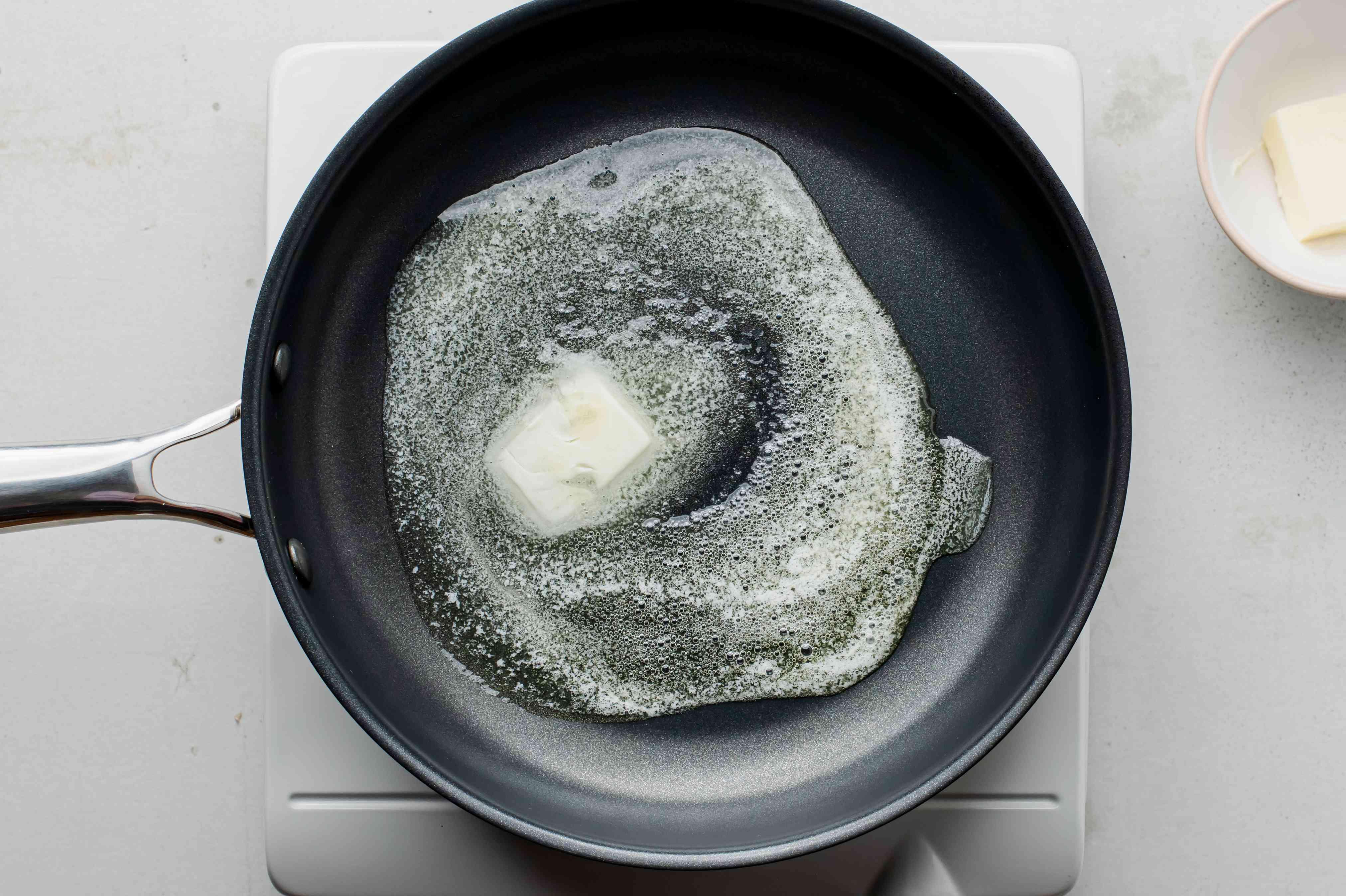 Butter melting in a black nonstick skillet