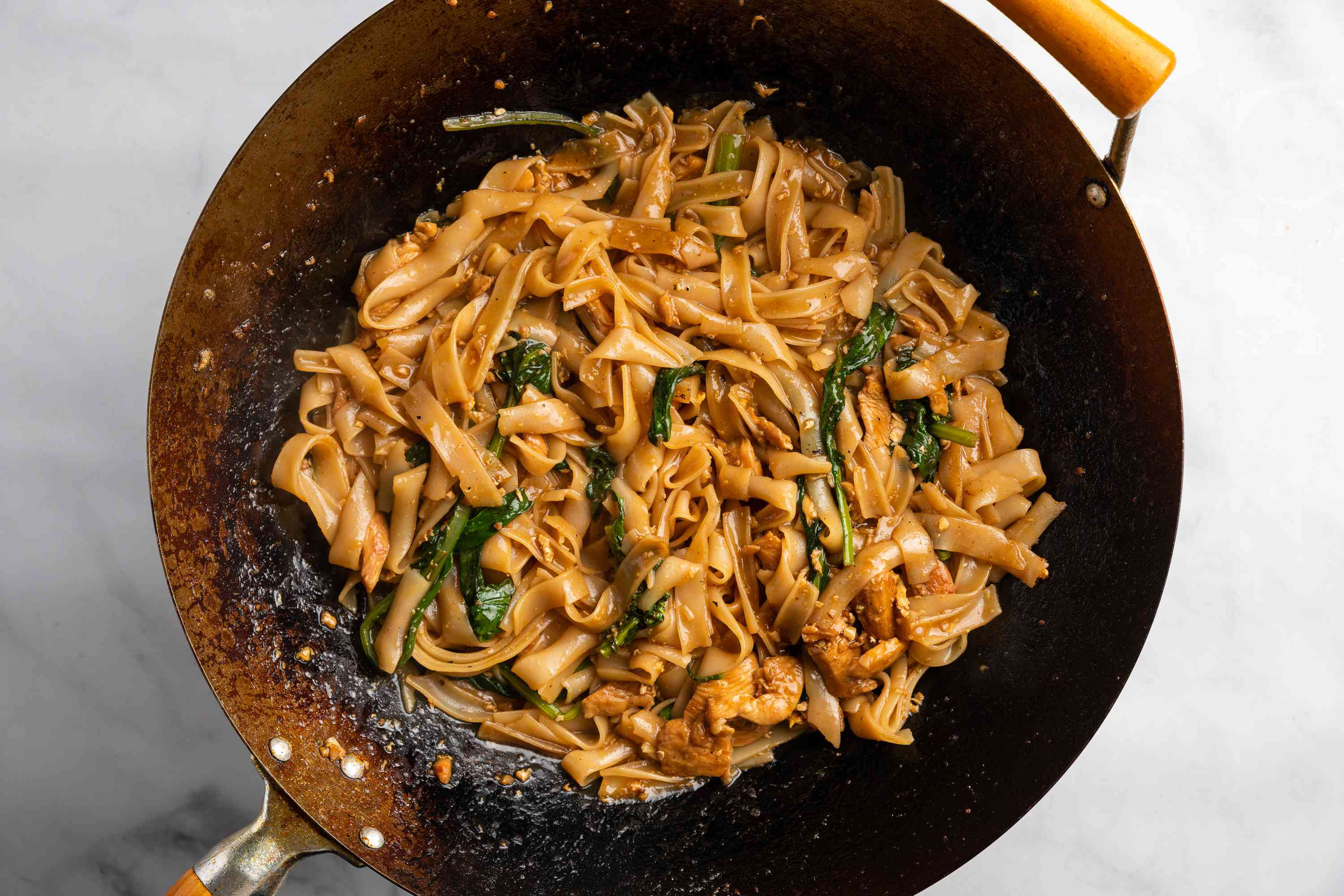 Stir fry ingredients together with noodles for chicken pad see ew