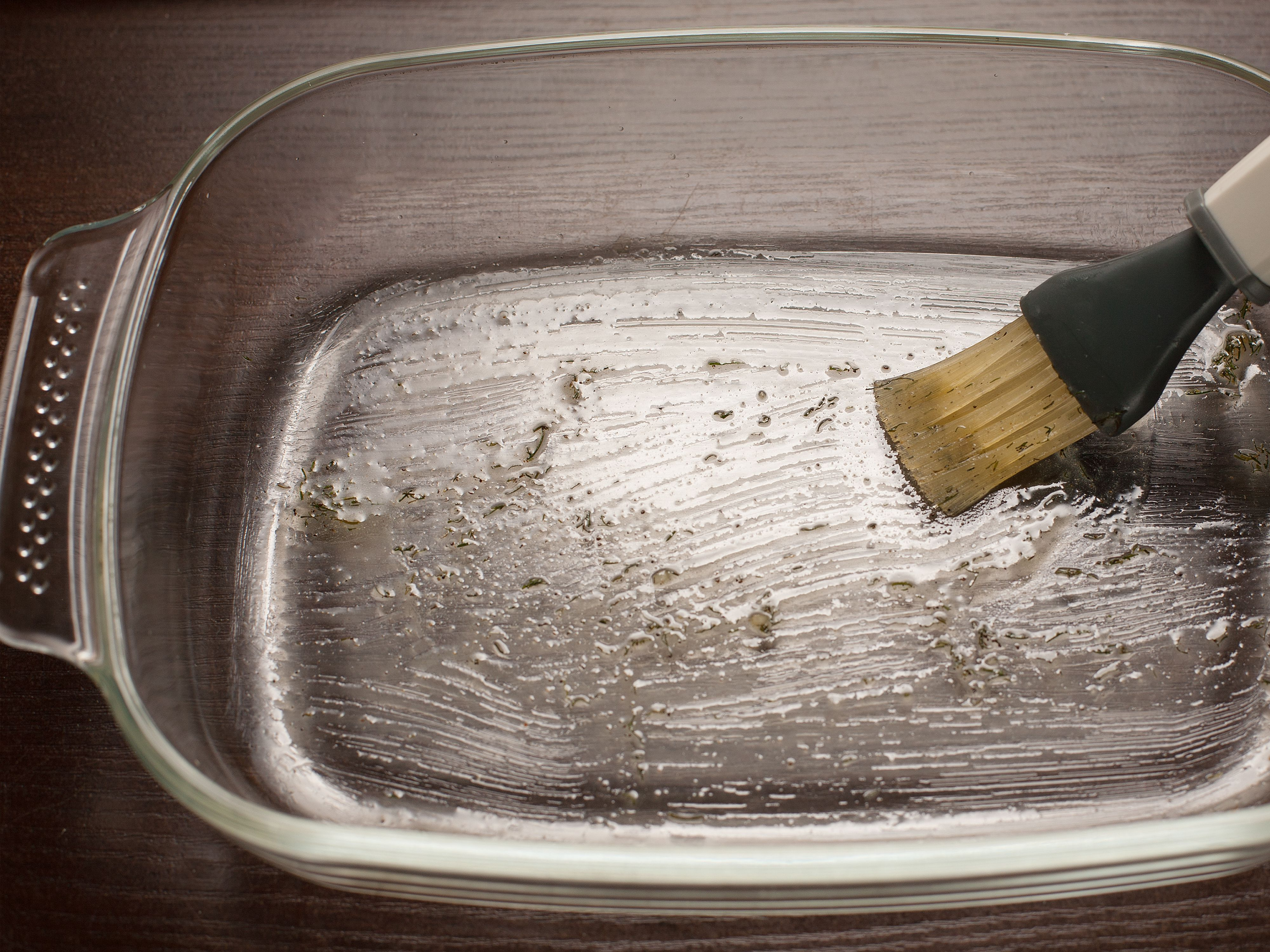Brushing a baking dish with butter.