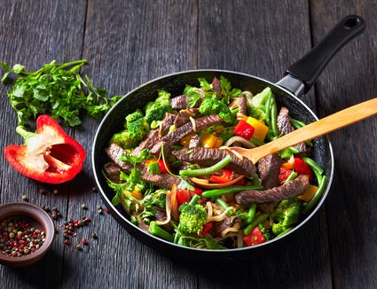 Fajita beef strips with vegetables: yellow and red sweet peppers, parsley, onion, green bean, and broccoli - stock photo