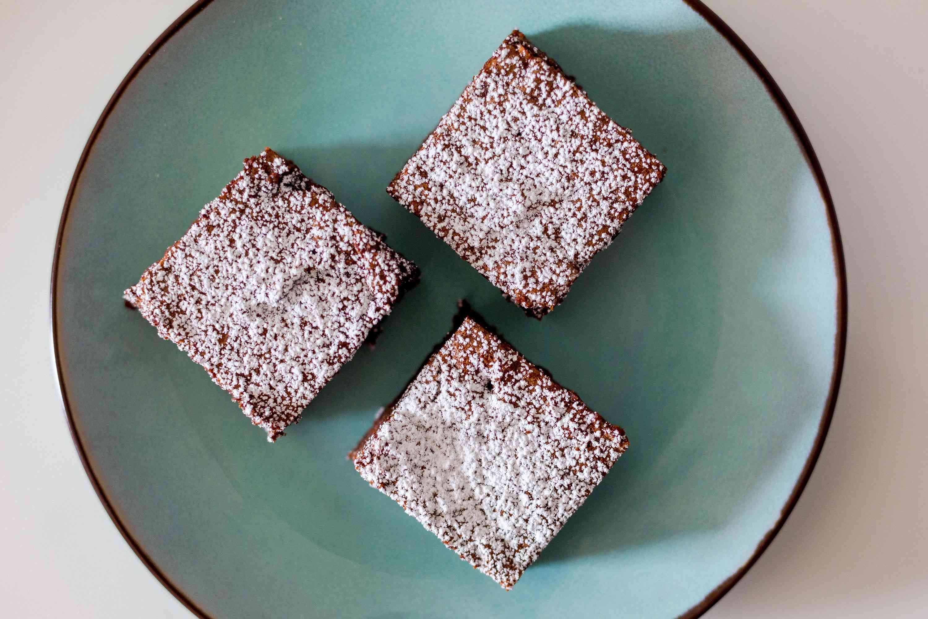 Slices of vegan Mexican chocolate cake topped with powdered sugar
