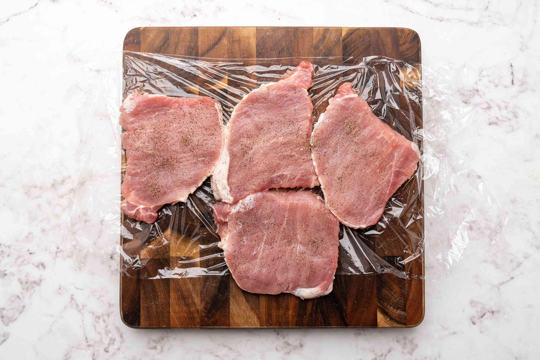 pork between pieces of plastic wrap