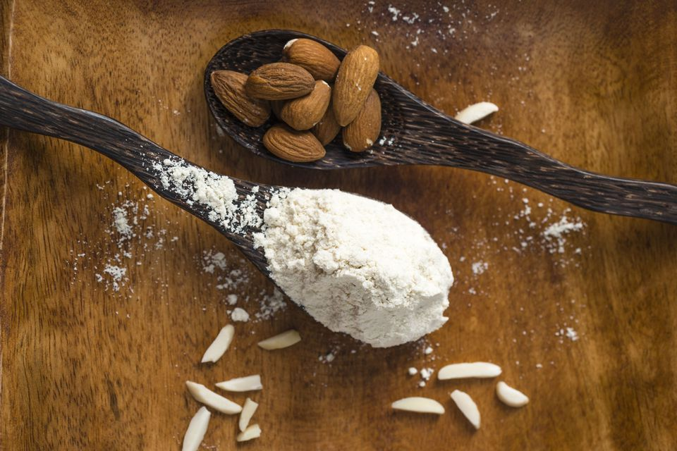 Almonds and almond flour on wooden spoons