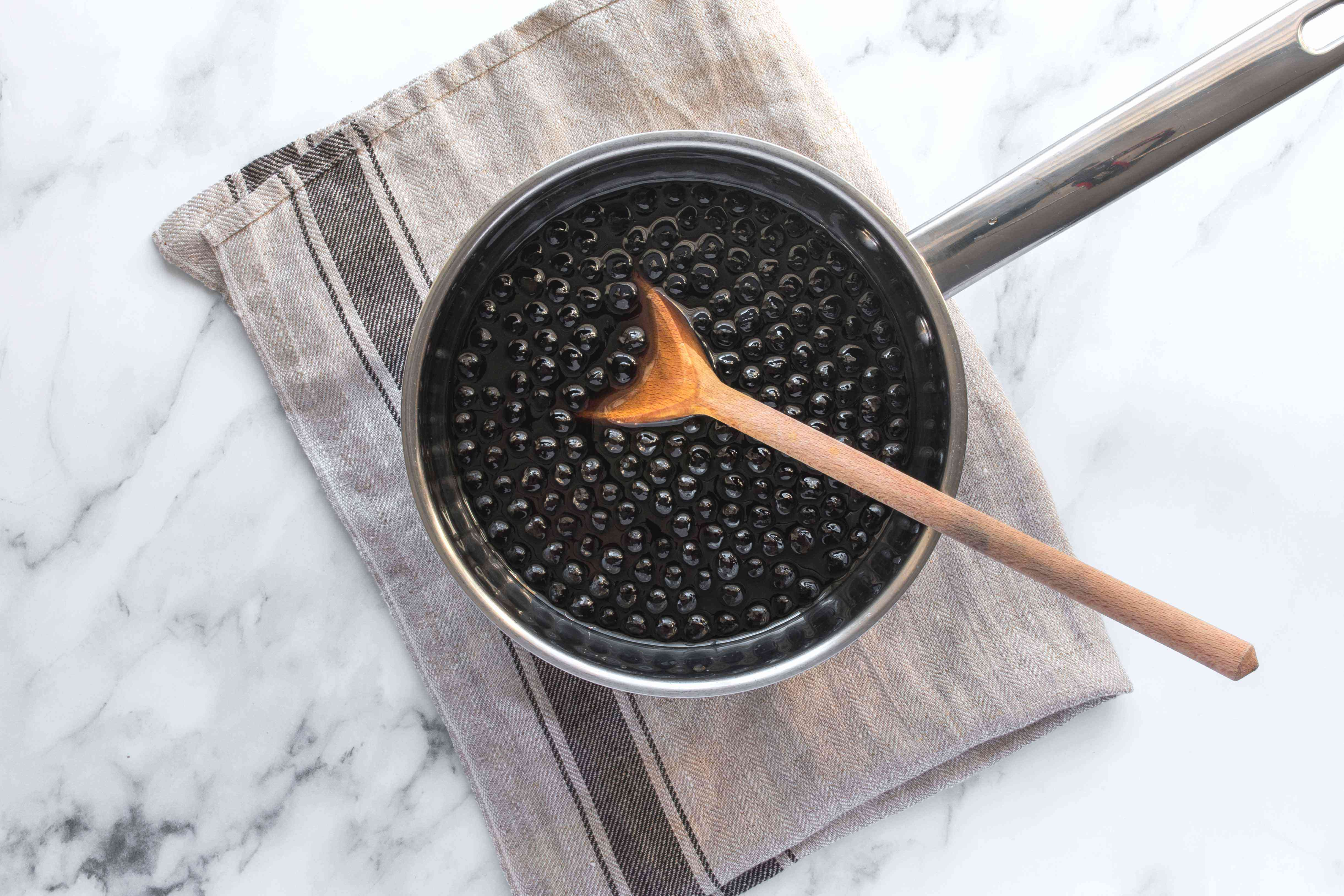 Pearls placed in saucepan with wooden spoon.