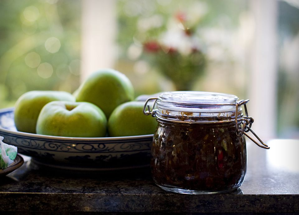 Mincemeat in jar in front of bowl of green tomatos