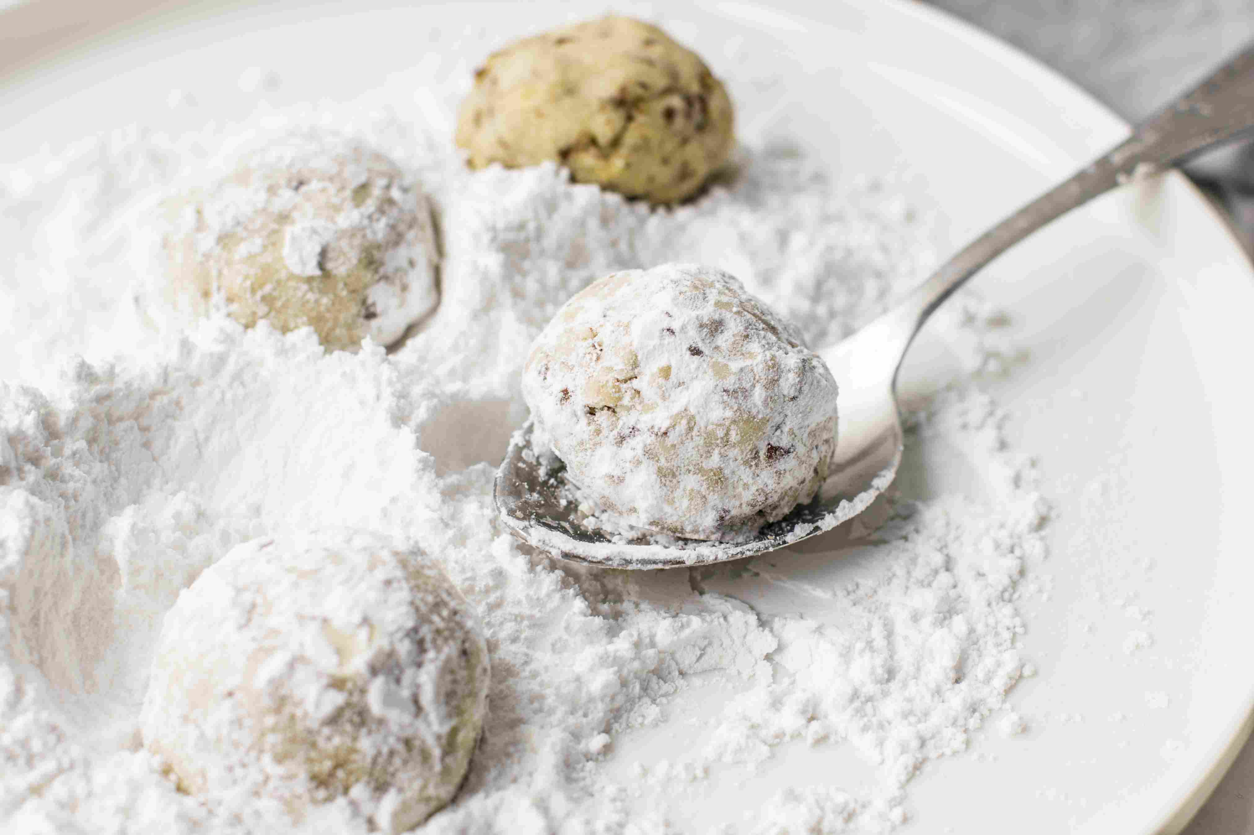 Cooked Pecan Butterball Cookies rolled into confectioner's sugar