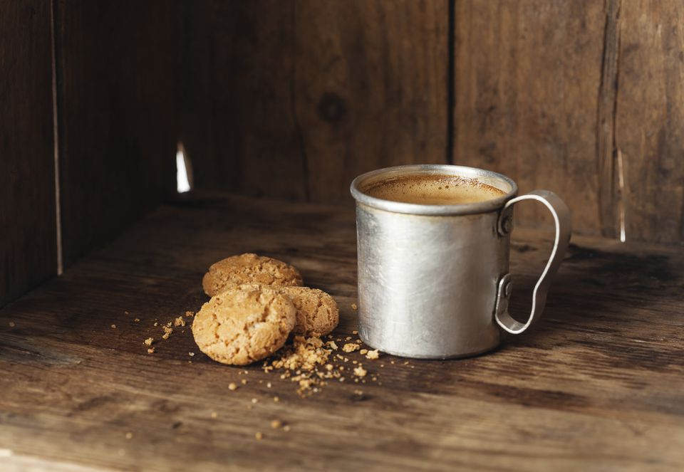 Gluten-free amaretti cookies paired with a hot drink in a metal mug