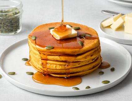 Stack of pumpkin pancakes on a plate with maple syrup, butter, and pumpkin seeds