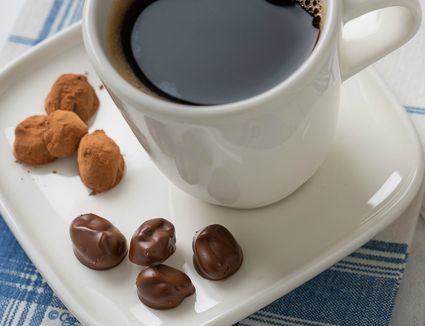 chocolate-covered coffee beans with cup of brewed coffee