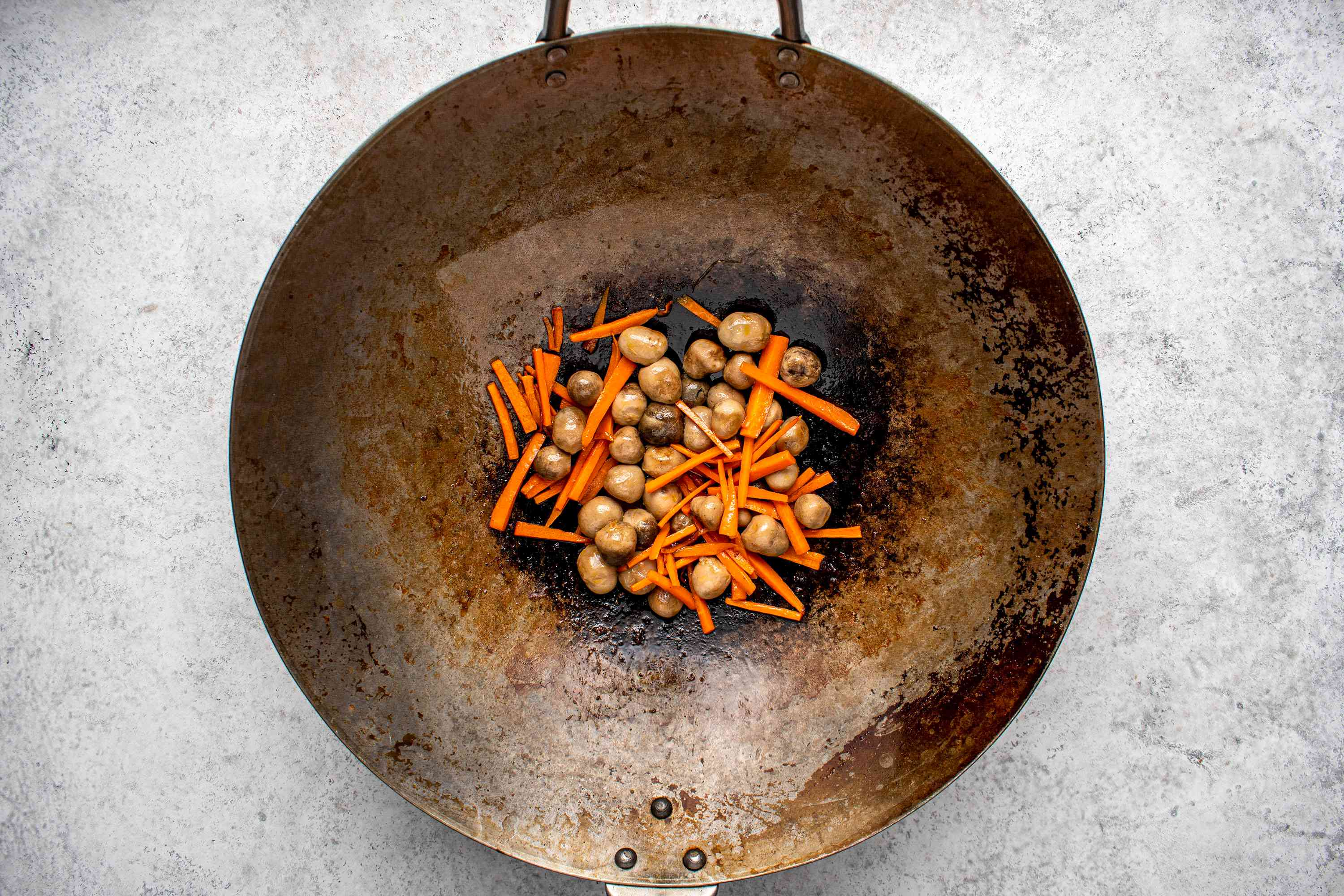 carrots and mushrooms cooking in a wok