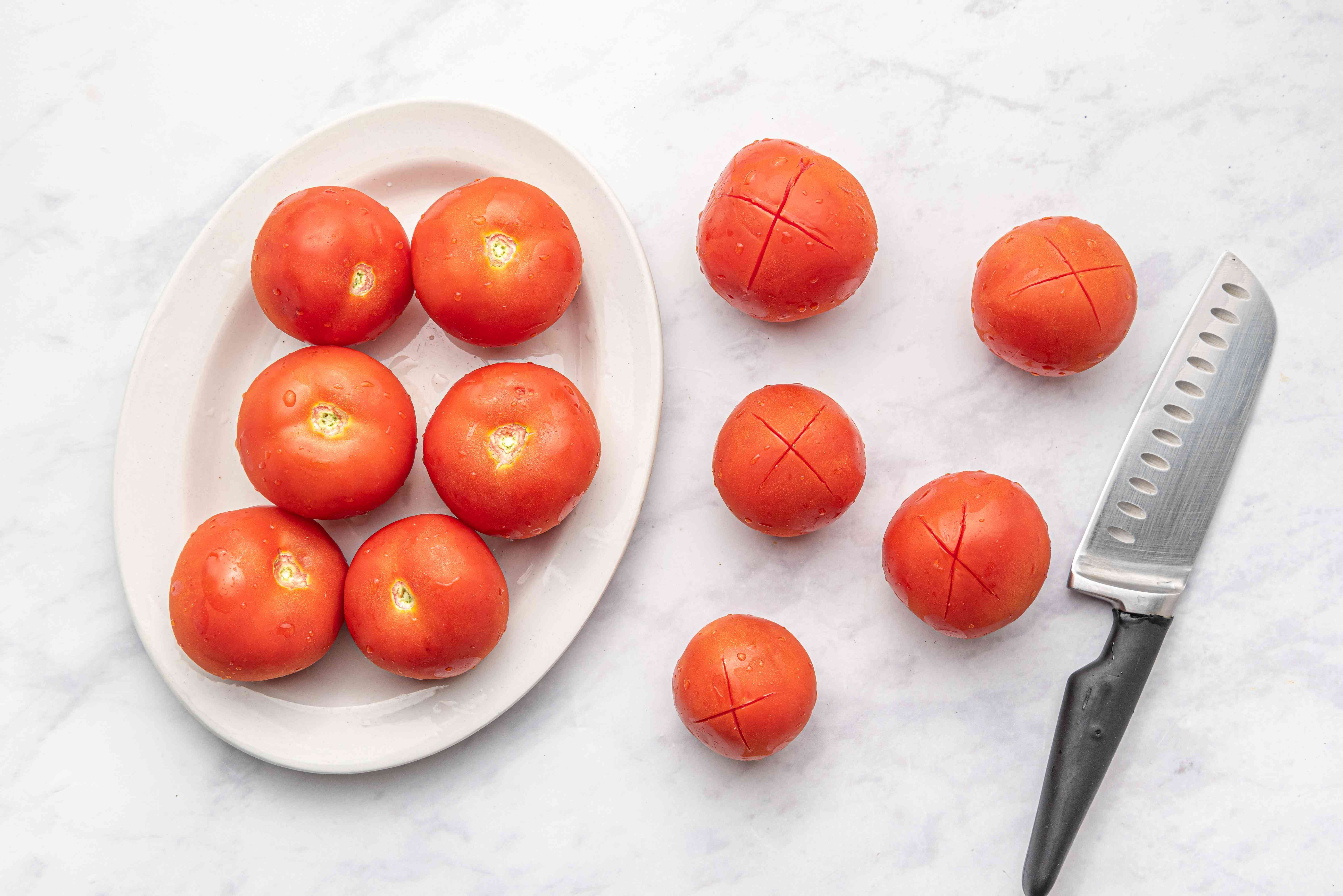 Make an X-shaped superficial cut at the bottom of each tomato