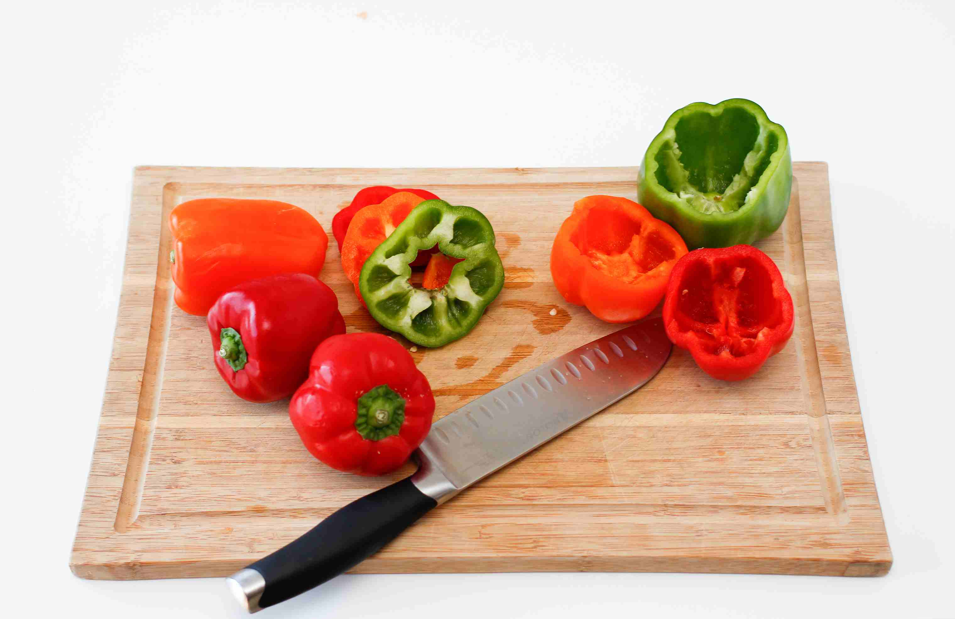 Bell peppers with tops removed on a cutting board with a knife