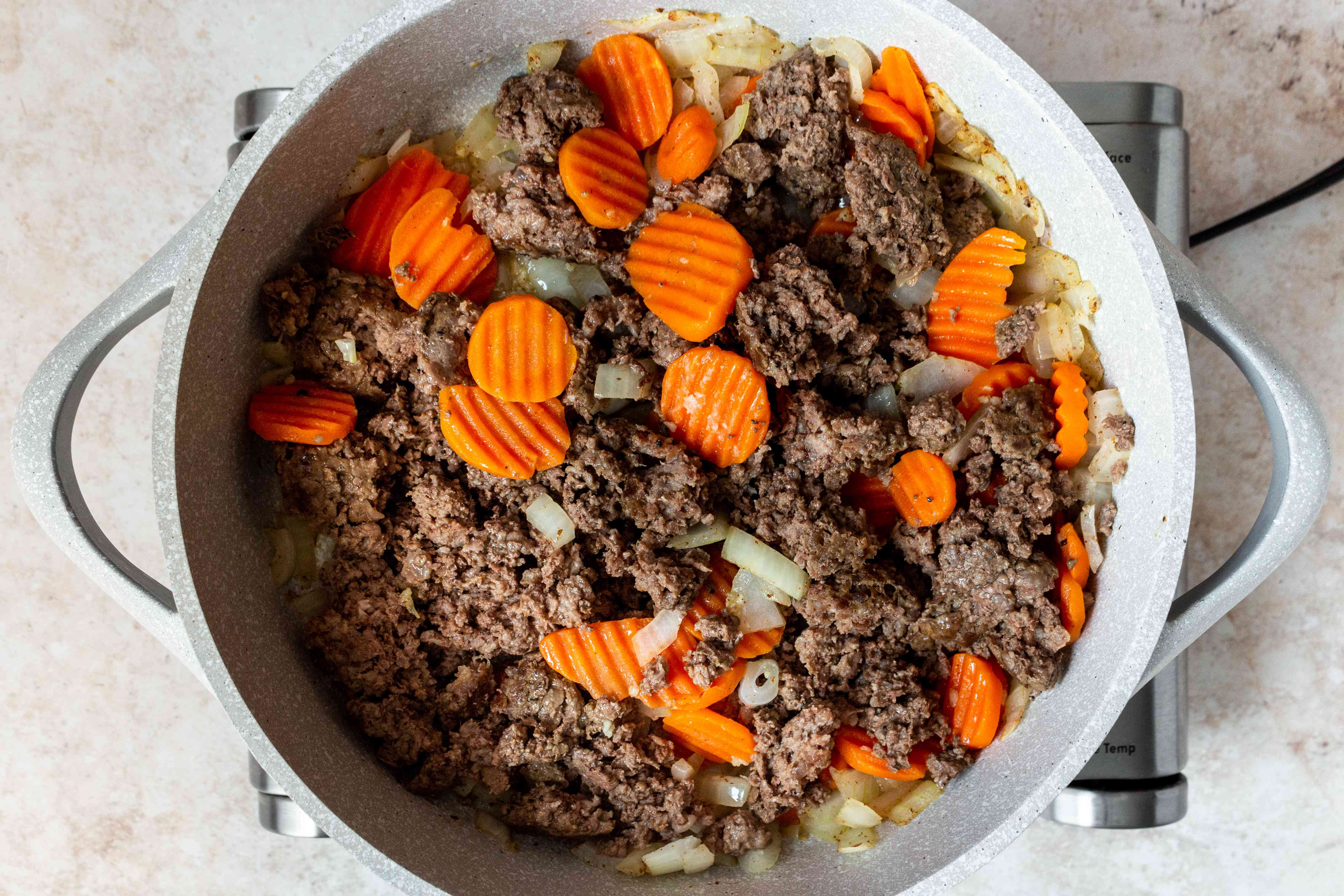 crumbled meatloaf added to the carrot and onion mixture in the skillet