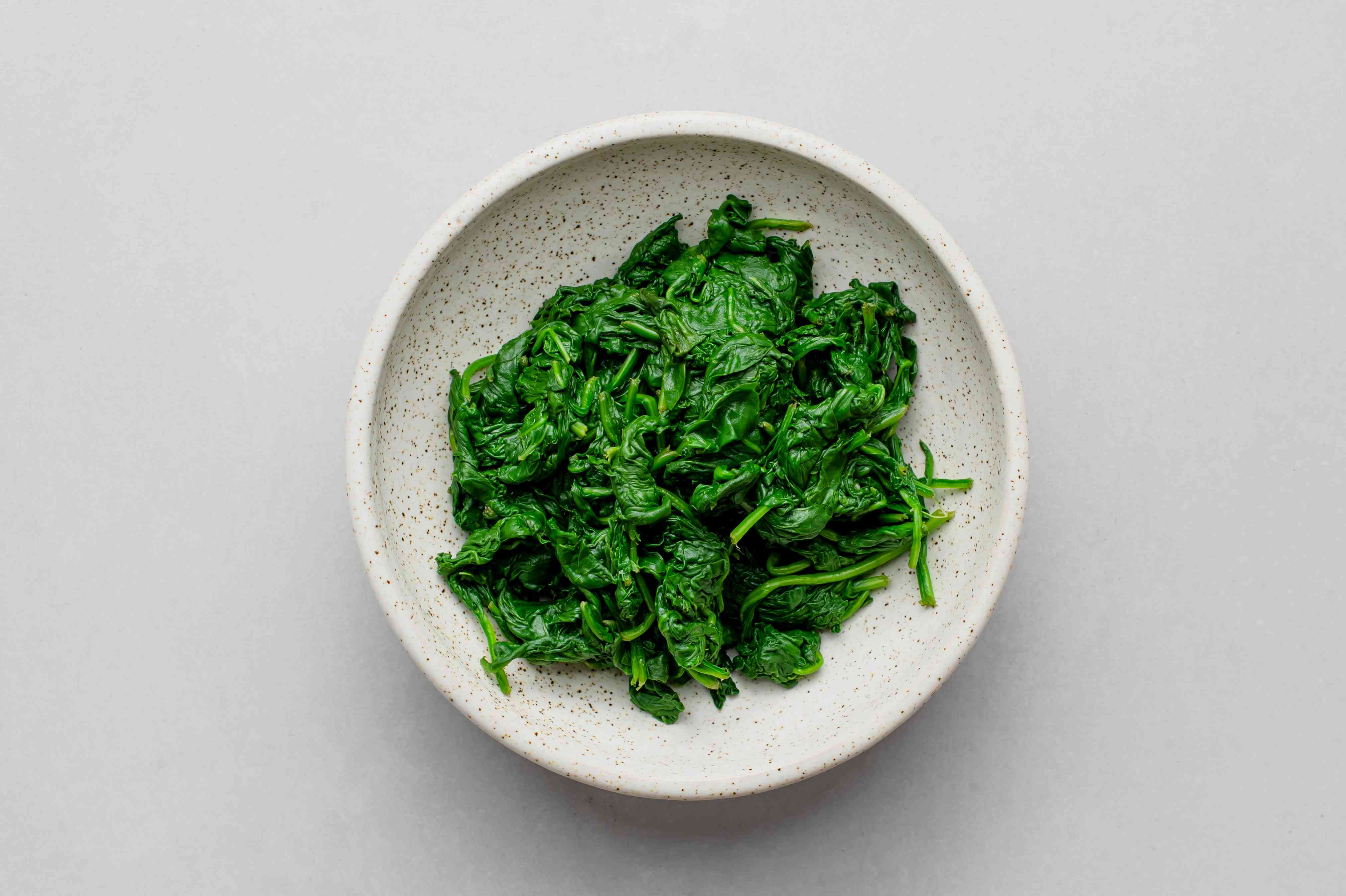 squeeze the spinach to remove excess water and transfer to a serving bowl