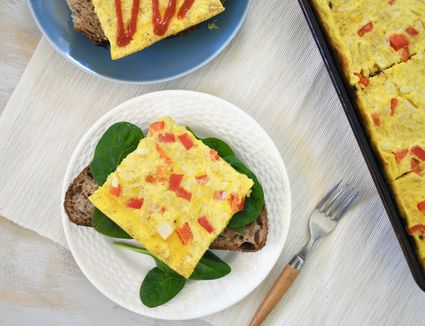Sheet pan eggs, slice served on a plate over toast and spinach