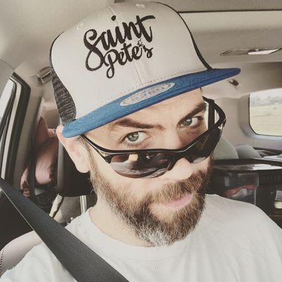 white man with sunglasses and hat and beard in a car with a seatbelt looking at the camera